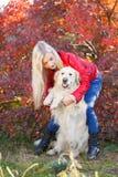 Довольно белокурая девушка идя с собакой в концепции животного леса Стоковое фото RF