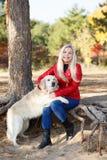 Довольно белокурая девушка идя с собакой в концепции животного леса Стоковое Фото