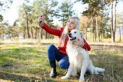 Довольно белокурая девушка идя с собакой в концепции животного леса Стоковая Фотография