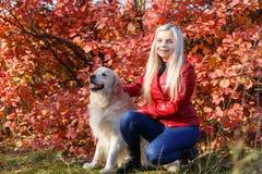 Довольно белокурая девушка идя с собакой в концепции животного леса Стоковое Изображение