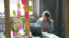 Довольно белокурая девушка слушает к музыке и работает с компьтер-книжкой в славном офисе просторной квартиры Она делает примечан сток-видео