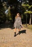Довольно белокурая модель с длинными волосами в платье knit и теплом пальто w Стоковая Фотография