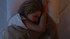 Довольно дама поворачивая в кровать, мигающие огни фестиваля вне спать прерывания видеоматериал