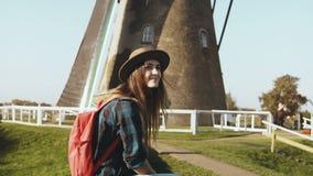 Довольно европейская туристская девушка около старой мельницы ветра Красивая молодая женщина в шляпе с длинными волосами сидит ок сток-видео