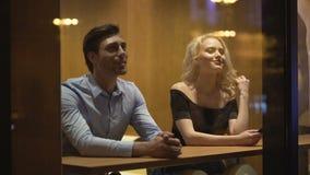 Довольно женский flirting с молодым человеком на кафе, выравнивая время, приемистость и дату сток-видео