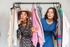 2 довольно заботливых молодой женщины выбирая одежды Стоковое Фото