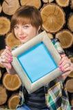 Довольно коротк-с волосами девушка держит рамку с местом для конца-вверх текста на предпосылке деревянных журналов Стоковая Фотография RF