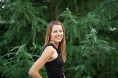 Довольно красивая усмехаясь женщина в черной рубашке при длинные волосы блеска представляя около елевого дерева во время летних к Стоковые Изображения