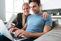 Довольно красивый человек и женщина используя портативный компьютер Стоковая Фотография RF