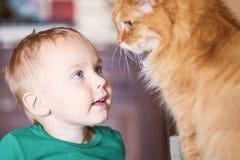 Довольно меньший кавказский ребенок со светлыми волосами, яркими голубыми глазами и красным взглядом кота на одине другого стоковые изображения rf