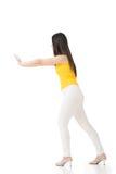 Довольно молодая азиатская женщина нажимая или полагаясь на стене. стоковые изображения rf