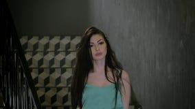 Довольно молодая кавказская девушка модели с длинными темными волосами элегантными идут вниз с лестниц смотря камеру исправляет е акции видеоматериалы