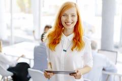 Довольно молодая красная женщина волос используя цифровую таблетку Стоковая Фотография
