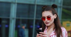 Довольно молодая модель в красных солнечных очках принимает selfie на ее smartphone сток-видео