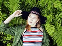 Довольно молодой белокурый битник девушки в шляпе среди папоротника, каникул в g Стоковое Изображение RF