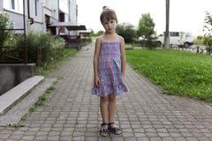Довольно молодой меньшая белокурая несчастная унылая friendless девушка ребенка в случайном платье лета стоя самостоятельно на со стоковое фото rf