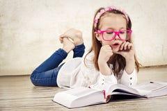 Довольно молодой учебник чтения школьницы и нося стекла стоковое фото