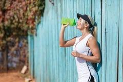 Довольно молодые женские глаза питьевой воды теннисиста закрыли Стоковое фото RF