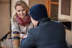 Довольно молодые пары сидя на кафе смотря один другого Стоковые Фотографии RF