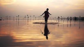Довольно, платье молодой женщины вкратце и солнечные очки бежать на пляже во время красивого захода солнца 1920x1080 акции видеоматериалы
