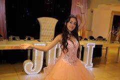 Довольно предназначенная для подростков девушка дня рождения quinceanera празднуя в партии пинка платья принцессы, специальном то Стоковые Фотографии RF