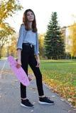 Довольно предназначенная для подростков девушка стоя держащ доску конька стоковые изображения rf