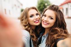 Довольно предназначенные для подростков девушки с стилями причёсок и губами красного цвета усмехаясь на камере Стоковые Фото
