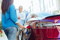 Довольно привлекательная женщина дозаправляя ее автомобиль Стоковые Изображения RF