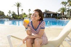Довольно привлекательная латинская женщина выпивая апельсиновый сок на бассейне Стоковые Изображения