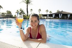 Довольно привлекательная латинская женщина выпивая апельсиновый сок на бассейне Стоковые Фотографии RF