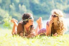 Довольно свободные девушки hippie кладя на траву - винтажный пэ-аш влияния Стоковое фото RF