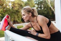 Довольно сильная женщина спорт детенышей делает протягивать спорт Стоковые Изображения RF