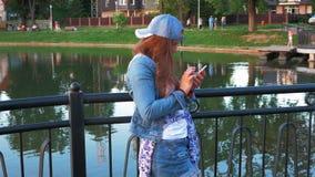 Довольно счастливая женщина используя smartphone в парке города, съемке steadicam акции видеоматериалы