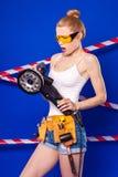Довольно, тонкая девушка построителя в белой рубашке, поясе построителя, построителе Стоковое фото RF