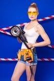 Довольно, тонкая девушка построителя в белой рубашке, поясе построителя, построителе Стоковое Фото