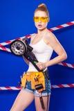 Довольно, тонкая девушка построителя в белой рубашке, поясе построителя, построителе Стоковая Фотография