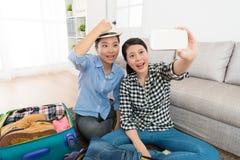 Довольно усмехаясь женские друзья пакуя багаж Стоковое Изображение RF