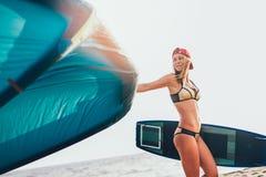 Довольно усмехаясь кавказское kitesurfer женщины идя на пляж Стоковые Фотографии RF