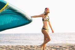 Довольно усмехаясь кавказское kitesurfer женщины идя на пляж Стоковые Фото