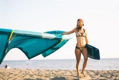 Довольно усмехаясь кавказское kitesurfer женщины идя на пляж Стоковые Изображения