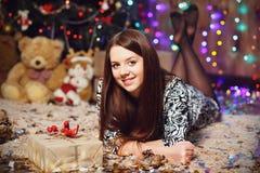 Довольно усмехаясь предназначенная для подростков девушка с длинными волосами в интерьере с Christm Стоковые Фото