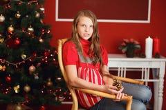 Довольно усмехаясь предназначенная для подростков девушка с длинными волосами в интерьере с Christm Стоковая Фотография