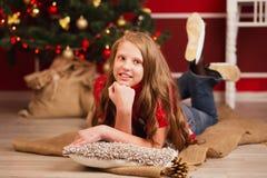 Довольно усмехаясь предназначенная для подростков девушка с длинными волосами в интерьере с Christm Стоковые Изображения RF