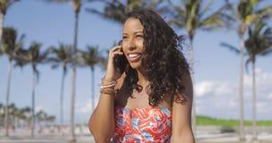 Довольно этническая женщина говоря на smartphone в летнем времени сток-видео
