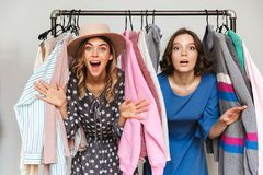 Довольно excited shopaholics молодых женщин выбирая одежды Стоковое Фото