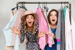 Довольно excited shopaholics молодых женщин выбирая одежды Стоковое Изображение