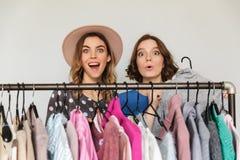 Довольно excited shopaholics молодых женщин выбирая одежды Стоковые Изображения RF