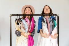 Довольно excited shopaholics молодых женщин выбирая одежды Стоковая Фотография RF