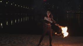 Довольно firegirl жонглируя освещенными факелами сидя вниз