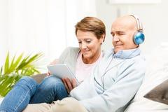Довольные пожененные пары ослабляя совместно дома Стоковая Фотография RF